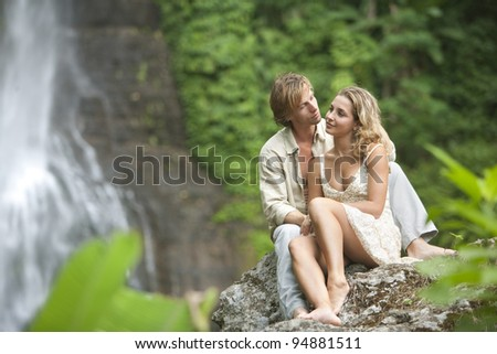Couple being affectionate while sitting down by tropical waterfalls. - stock photo