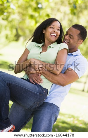 Couple being playful outdoors smiling - stock photo