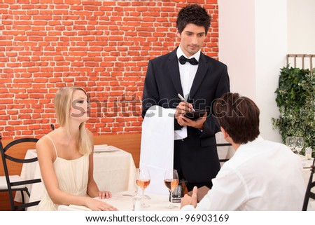 Couple being served by a waiter - stock photo
