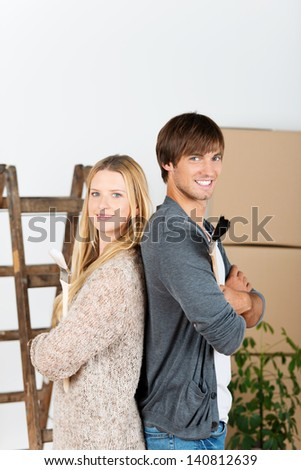 couple between transport boxes, with brushes in hand - stock photo