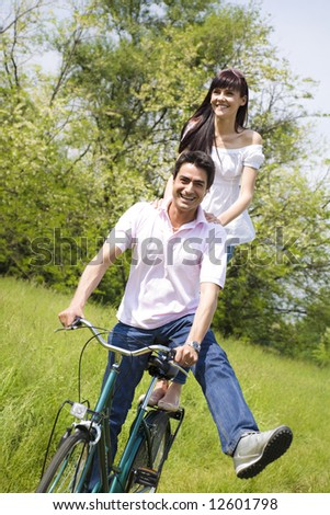 couple biking in park, smiling and hands on shoulder - stock photo