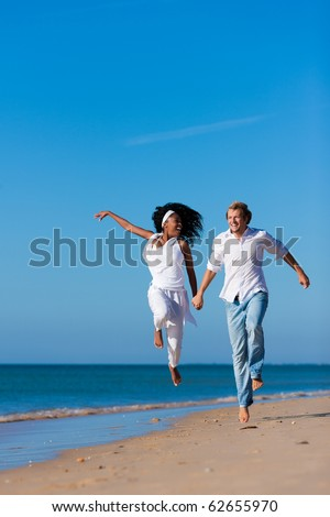 Couple - black woman and Caucasian man � having a walk jumping on a beach in their vacation - stock photo