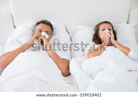 Couple Blowing Their Nose While Sleeping In Bed - stock photo