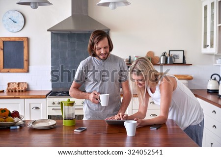couple bonding and enjoying morning coffee with tablet computer in kitchen at home - stock photo