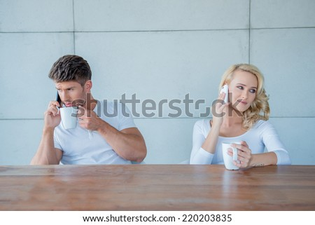 Couple both using their mobile phones simultaneously as they sit at a wooden counter enjoying their morning coffee - stock photo