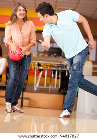 Couple bowling with a man teaching a woman how to swing