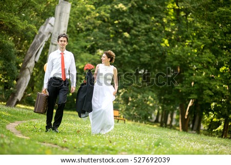 couple bride and groom walking on a park background.