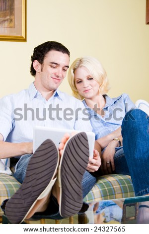 Couple browsing internet on laptop at home