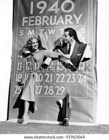 Couple bursting through leap year calendar - stock photo