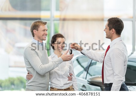 Couple buying a car indoors - stock photo