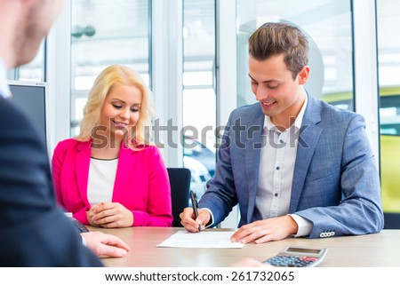 Couple buying car at dealership and signing sales contract with salesman - stock photo