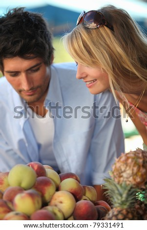 Couple buying fruit at a local market - stock photo