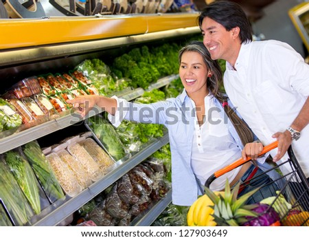 Couple buying groceries at the local store - stock photo