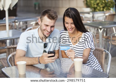 Couple buying online on holidays with a laptop and credit card on terrace bar - stock photo