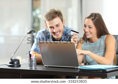 Couple buying online together with a laptop on a desktop at home - stock photo