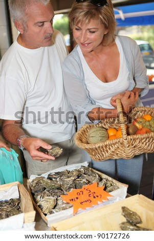 Couple buying oysters - stock photo