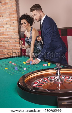 Couple by roulette table at casino - stock photo