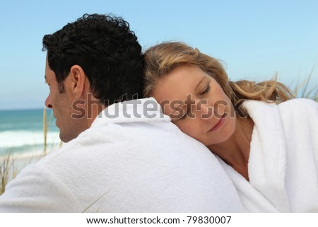 Couple by the sea in toweling robes - stock photo