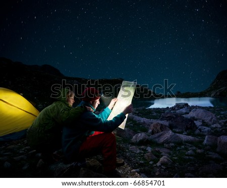 couple camping at night - stock photo