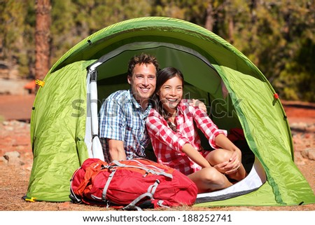 Couple camping in tent happy in romance smiling happy outdoors in forest enjoying love looking at view. Happy interracial couple relaxing after outdoor activity hiking. Asian woman, Caucasian man. - stock photo
