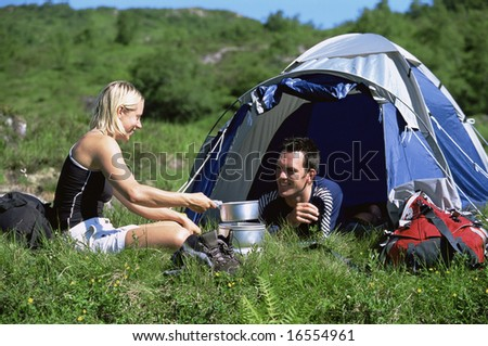 Couple camping in the great outdoors - stock photo