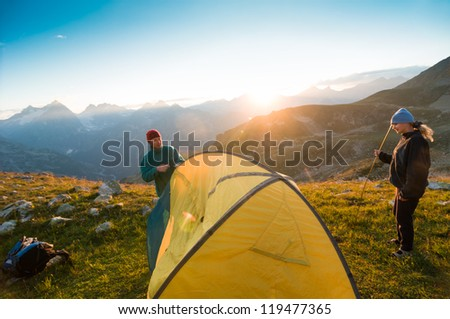 couple camping with tent in mountains - stock photo