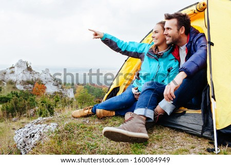 Couple camping. Young people sitting in tent watching the view - stock photo
