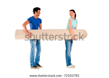 couple carrying a carpet - stock photo