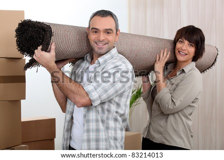 Couple carrying carpet over shoulders - stock photo