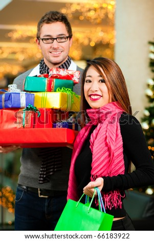 Couple - Caucasian man and Asian woman - with Christmas presents, gifts and shopping bags - in a mall in front of a Christmas tree