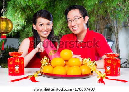 Couple celebrate Chinese new year traditional with gift, wearing red shirts - stock photo
