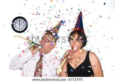 Couple celebrates a happy occasion by wearing party hats and blowing horns - stock photo