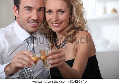 Couple celebrating at home with champagne - stock photo