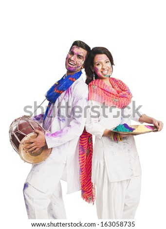 Couple celebrating Holi with colorful paints and a drum - stock photo