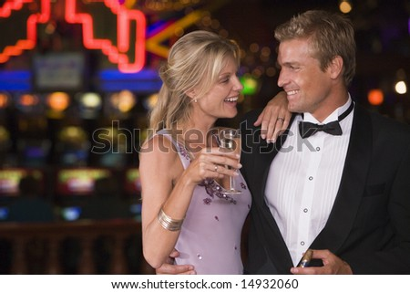 Couple celebrating in casino with champagne