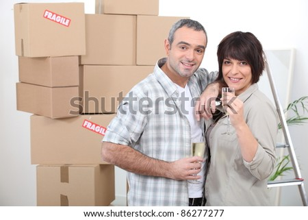 Couple celebrating moving in with champagne - stock photo