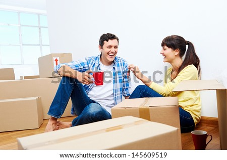 couple celebrating new home handing keys and moving boxes