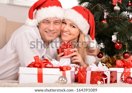 Couple celebrating New Year at home lying on carpet with gifts - stock photo