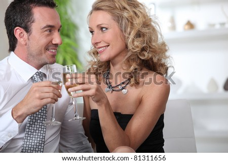 Couple celebrating with a glass of champagne - stock photo