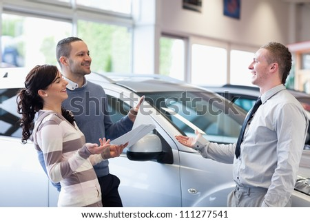 Couple chatting with a salesman in a car shop - stock photo