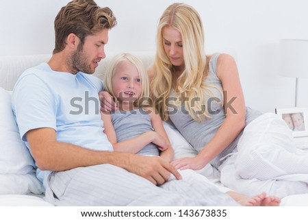 Couple chatting with their daughter in bed