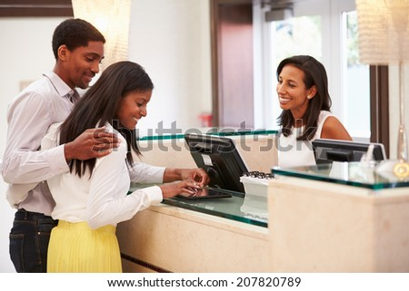 Couple Checking In At Hotel Reception Using Digital Tablet - stock photo