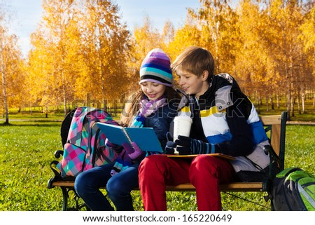 Couple children, boy and girl sitting on the bench in autumn park reading a textbook with smile on the face - stock photo