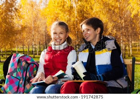 Couple children, boy and girl sitting on the bench in autumn park talking and laughing on sunny day - stock photo