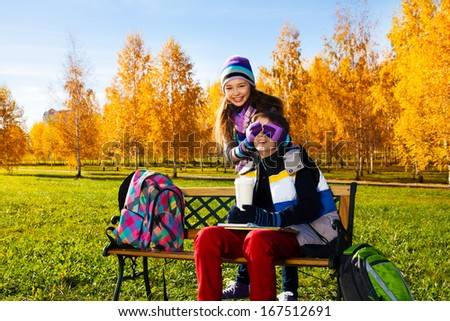 Couple children, girl covers boys face with palms and laughing making a surprise, guy sitting on the bench in autumn park - stock photo
