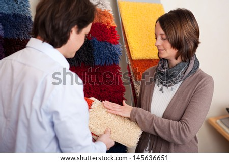 Couple choosing a carpet holding up a sample swatch in her hands while discussing it with a decorator or salesman - stock photo
