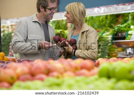 Couple choosing apples in grocery store - stock photo
