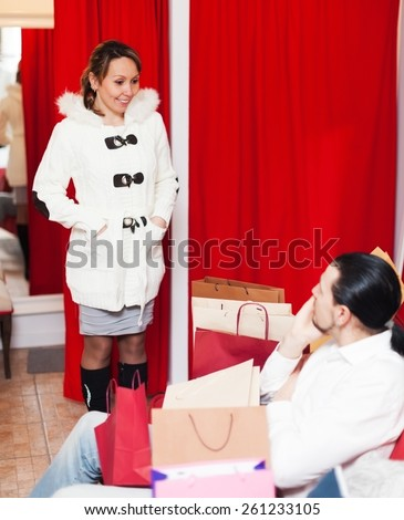 Couple choosing coat in fitting-room at market together - stock photo