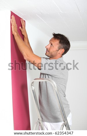 Couple choosing color of new wallpaper - stock photo