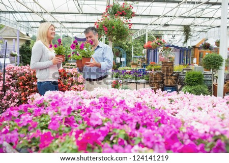 Couple choosing flowers in the garden centre while talking - stock photo